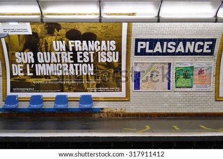 PARIS, FRANCE -8 JULY 2015- The Plaisance station, on Line 13 of the Paris metro subway, is located in the 14th arrondissement. A poster for an exhibit about France and immigration is on the platform. - stock photo