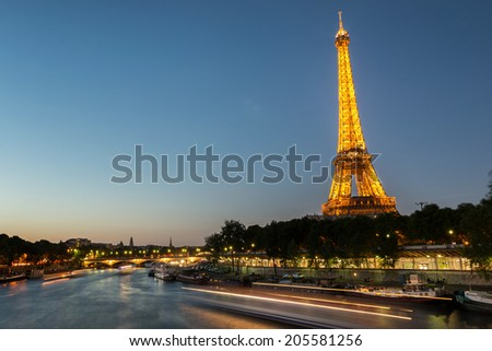 PARIS, FRANCE- 12 June, 2014: Eiffel tower at night with a boat passes on River Seine. The Eiffel tower is one of the landmarks of Paris.