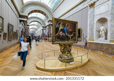 PARIS, FRANCE - June 13, 2014: Interior view of Paris Louvre Museum gallery when visitors walk and browse the collection.  - stock photo
