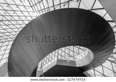 PARIS, FRANCE - June 13, 2014:Louvre Pyramid view from below angle with architectural details of glass steel and Stairs with counter sun light in black and white. - stock photo