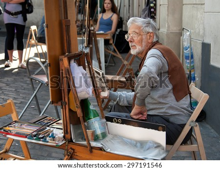 PARIS, FRANCE - JUNE 07, 2010: Painter and his easel in Place du Tertre of Montmartre, which is a cobbled square and a hangout for buskers and artists painting landscapes and tourist portraits. - stock photo