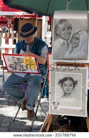 PARIS, FRANCE - JUNE 07, 2010: Parisian artist drawing a caricature in Place du Tertre of Montmartre, which is a famous hangout for buskers and artists painting landscapes and tourist portraits. - stock photo