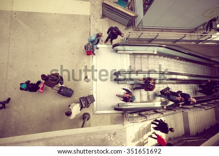 PARIS, FRANCE - JUNE 1, 2015: Passengers in the electric escalators in the Gare du Nord station in Paris, the busiest railway station of Europe. Color toned shot - stock photo