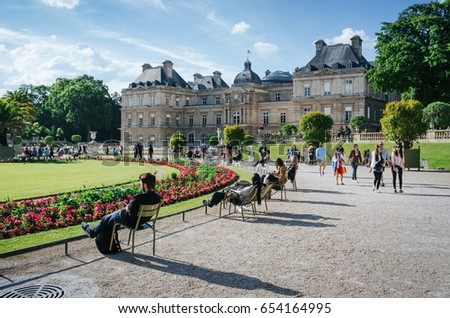 PARIS, FRANCE - JUNE 26, 2016: People relax and hang out in picturesque park in front of Palais du Luxembourg or Luxemburg Palace on bright summer sunny day.