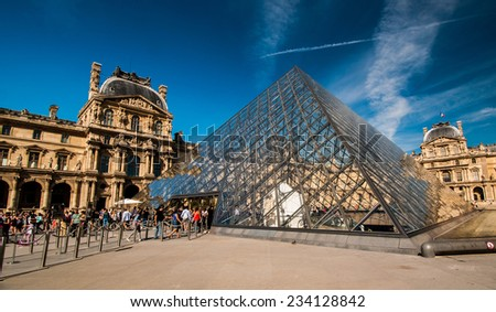 PARIS, FRANCE - JUNE 18 , 2014: Tourists in the Louvre's central courtyards with the Louvre pyramid and palace. The Louvre is the world's most visited museum - stock photo