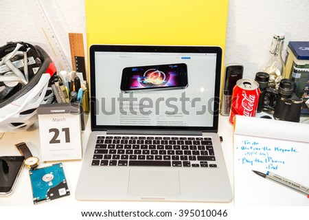 PARIS, FRANCE - MARCH 21, 2016: Apple Computers website on MacBook Pro Retina in a geek creative room environment showcasing the newly announced iPhone SE and its Chip - stock photo