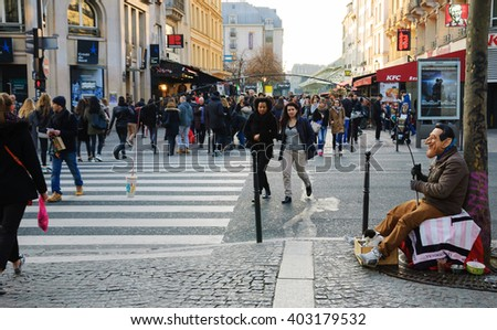 PARIS, FRANCE - MARCH 12, 2016: Man in mask fishing (begging) for money in city center. Beggars work in the most popular shopping and tourist hotspots of Paris. Selective focus on the mask. - stock photo