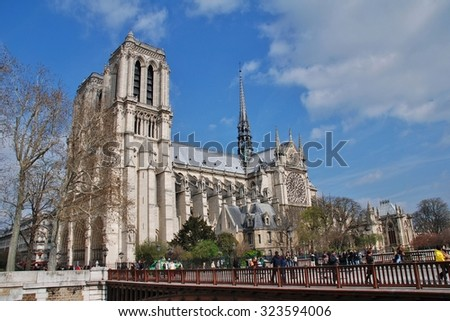 PARIS, FRANCE - MARCH 18, 2014: People walk across the Pont au Double in front of the historic Notre Dame cathedral. Started in 1120, the Catholic cathedral was completed in 1345. - stock photo