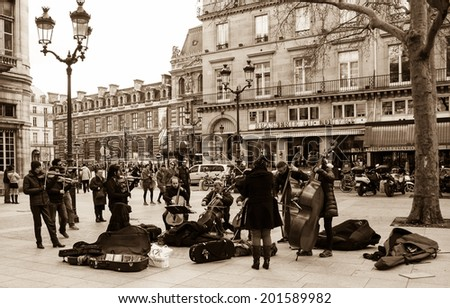 PARIS, FRANCE - MARCH 3, 2014: Small string orchestra plays at Comedie Francaise square before audience consisting mainly of tourists. Dozens buskers perform on the streets and in metro of Paris. - stock photo