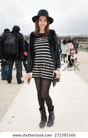 PARIS, FRANCE - MARCH 10, 2015: Stylish Asian woman with black and white strip skirt in the Tuileries Garden. Paris Fashion Week: Ready to Wear 2015/2016 is held from March 3 to 11, 2015. - stock photo