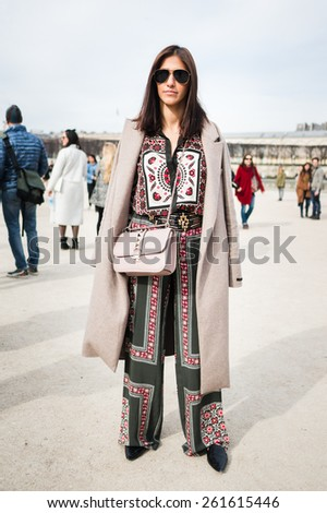 PARIS, FRANCE - MARCH 7, 2015: Stylish European woman with colorful dress in the Tuileries Garden. Paris Fashion Week: Ready to Wear 2015/2016 is held from March 3 to 11, 2015. - stock photo