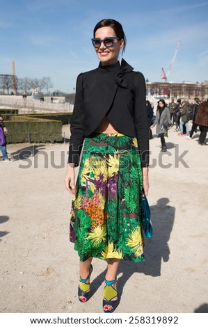 PARIS, FRANCE - MARCH 6, 2015: Stylish european woman with flower pattern skirt in the Tuileries Garden. Paris Fashion Week: Ready to Wear 2015/2016 is held from March 3 to 11, 2015. - stock photo