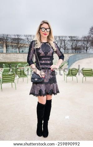 PARIS, FRANCE - MARCH 10, 2015: Stylish European woman with hollow out pattern in the Tuileries Garden. Paris Fashion Week: Ready to Wear 2015/2016 is held from March 3 to 11, 2015. - stock photo