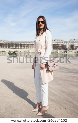 PARIS, FRANCE - MARCH 6, 2015: Stylish european woman with light brown robe in the Tuileries Garden. Paris Fashion Week: Ready to Wear 2015/2016 is held from March 3 to 11, 2015. - stock photo