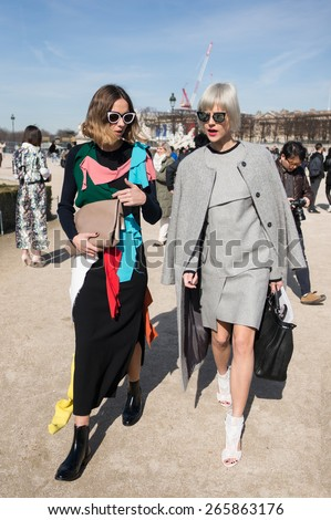 PARIS, FRANCE - MARCH 6, 2015: Stylish european women with colorful skirt in the Tuileries Garden. Paris Fashion Week: Ready to Wear 2015/2016 is held from March 3 to 11, 2015. - stock photo