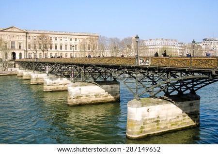 PARIS, FRANCE MARCH 17, 2015: The Pont des Arts or Passerelle des Arts is a pedestrian bridge in Paris which crosses the River Seine. - stock photo