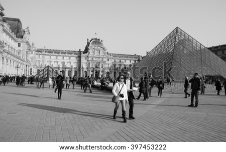 PARIS, FRANCE - MARCH 12, 2016: Tourists near Pyramid of Louvre at sunset. Louvre is the world's most visited museum receiving more than 9 million visitors each year. - stock photo