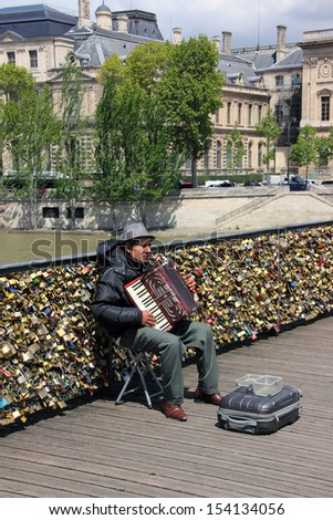 PARIS, FRANCE - MAY 23, 2013: An accordion player sitting on a bridge in Paris and plays French songs. Behind him is the bridge railing, full of thousands of love locks. - stock photo