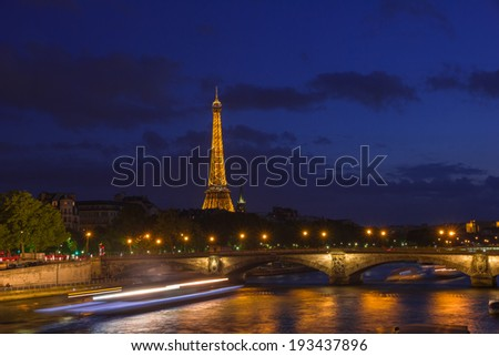 PARIS, FRANCE - MAY 9, 2014: Cityscape of Paris with Eiffel Tower (Tour Eiffel) and Pont des Invalides at night illumination. The Eiffel tower is the most famous and visited monument of France.