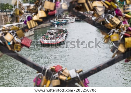 PARIS, FRANCE - MAY 29: Cruise ship with unknown tourists seen through love padlocks at a bridge over the Seine river on May 29, 2015 in Paris, France - stock photo