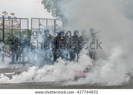 Paris, FRANCE - MAY 17, 2016 : French police, anti-riot squad, surrounded by tear gas during the massive protest over the labor law reforms. - stock photo