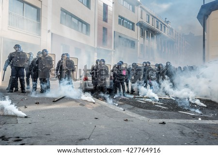 Paris, FRANCE - MAY 1, 2016 : French police, anti-riot squad,surrounded by tear gas during the massive protest over the labor law reforms. - stock photo