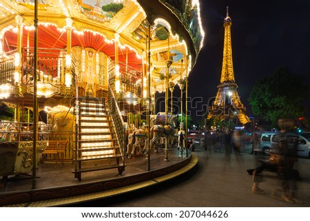 PARIS, FRANCE - MAY 17, 2014: Illuminated vintage carousel close to Eiffel Tower, Paris. - stock photo