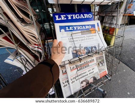 PARIS, FRANCE - MAY 9, 2017: Pov buying Le Figaro  newspaper front page with the picture of the newly elected French president Emmanuel Macron after the second round French Presidential election