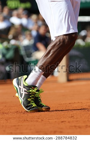 PARIS, FRANCE- MAY 27, 2015: Professional tennis player Gael Monfis wears custom Asics tennis shoes during second round match at Roland Garros 2015 in Paris, France