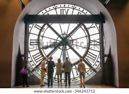 Paris, France - May 14, 2015: ?tourists looking through the clock with roman numerals in the museum D'Orsay. ?useum houses the collection of impressionist and post-impressionist masterpieces. - stock photo