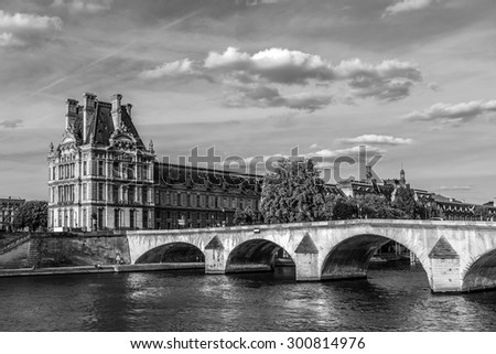 PARIS, FRANCE - MAY 30, 2015: View of famous Louvre Museum from the Seine River. Louvre Museum is one of the largest and most visited museums worldwide. Black and white.