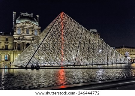 PARIS, FRANCE - MAY 15, 2014: View of illuminated buildings and pyramid in the courtyard of the Louvre Museum at night. The Louvre is one of the world's largest museums. - stock photo