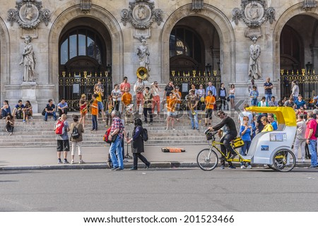 PARIS, FRANCE - MAY18, 2014: Young brass band near Paris Opera building (Garnier Palace) in Paris. Dozens buskers perform on the streets and in Paris metro. - stock photo
