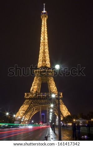 PARIS, FRANCE - NOV 2ND 2013: The Eiffel Tower and light trails crossing the Pont d'lena in Paris on November 2nd 2013.
