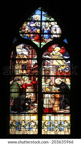 PARIS,FRANCE - NOV 11,2012:Saint Vincent de Paul raising a newborn and christening, stained glass.St Severin is Catholic church in the Latin Quarter. It is one of the oldest churches on the Left Bank. - stock photo