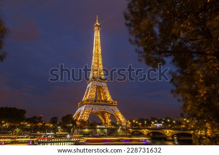 PARIS, FRANCE - NOVEMBER 1: A view of illuminated Eiffel Tower in the evening on November 1, 2014. Eiffel Tower is the most popular tourist attraction in France.  - stock photo
