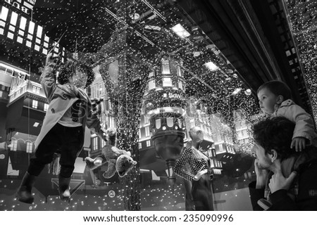 PARIS, FRANCE - NOVEMBER 22, 2014:  Christmas decoration (Magical journey by Burberry) in the windows of Printemps department store attracts Parisian children and tourists. - stock photo