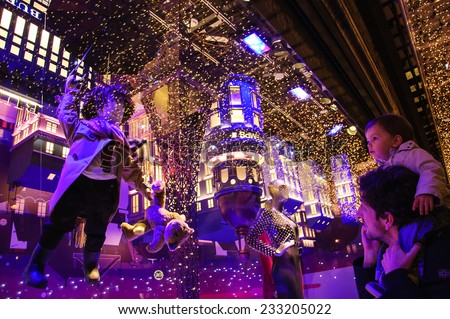 PARIS, FRANCE - NOVEMBER 23, 2014: Colorful Christmas decoration by Burberry in the windows of Printemps department store attracts Parisian children and tourists. - stock photo