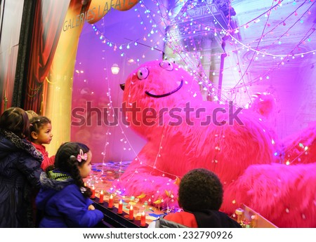 PARIS, FRANCE - NOVEMBER 23, 2014: Colorful Christmas decoration in the windows of Galeries Lafayette department store attracts Parisian children and tourists.