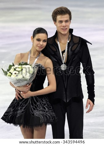 PARIS, FRANCE - NOVEMBER 16, 2013: Elena ILINYKH / Nikita KATSALAPOV of Russia pose during the victory ceremony in ice dance at Trophee Bompard ISU Grand Prix at Palais Omnisports de Bercy. - stock photo