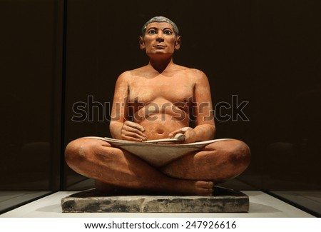 PARIS, FRANCE - NOVEMBER 15, 2013: Famous Egyptian statue of the Seated Scribe exhibited in the Louvre Museum in Paris, France. - stock photo