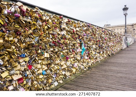 PARIS, FRANCE - NOVEMBER 28., 2014: Lovers have locked thousands of locks to the Pont des Arts bridge in Paris. The padlocks, with keys thrown into the Seine River, is a modern tradition.  - stock photo