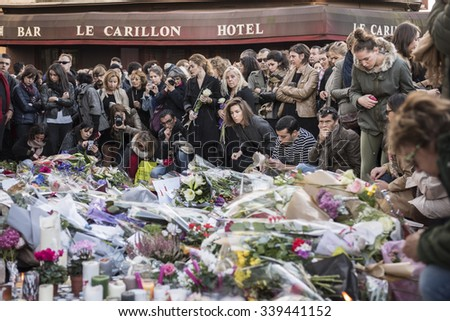 PARIS, FRANCE - NOVEMBER 14, 2015 :  People in front of the restaurant Le Petit Cambodge street Alliber in tribute to victims of the Nov. 13, 2015 in Paris at the Bataclan. - stock photo