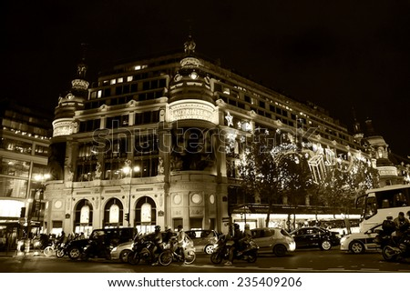 PARIS, FRANCE - NOVEMBER 22, 2014: Printemps department store decorated for Christmas by Burberry and traffic jam. Christmas decorations attracts Parisian children, tourists and shopping crowd. - stock photo