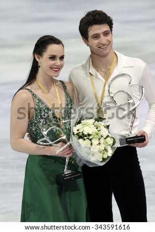 PARIS, FRANCE - NOVEMBER 16, 2013: Tessa VIRTUE / Scott MOIR of Canada pose during the victory ceremony in ice dance at Trophee Bompard ISU Grand Prix at Palais Omnisports de Bercy. - stock photo