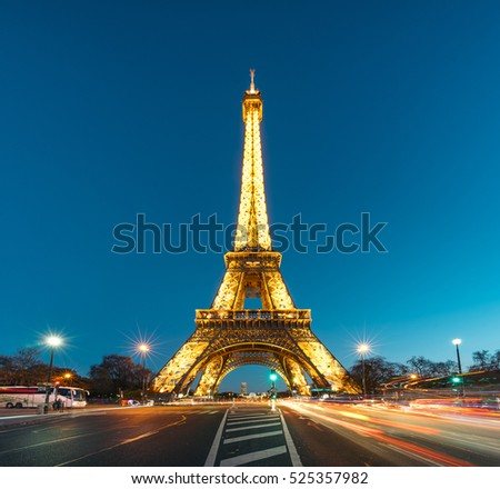 PARIS, FRANCE - NOVEMBER 29, 2016: The Eiffel Tower (Tour Eiffel) illuminated at dusk with traffic. It's a wrought iron lattice tower named after the engineer Gustave Eiffel.