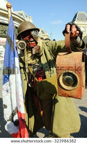 PARIS, FRANCE - OCTOBER 3, 2015: A man in costume of zombie soldier with French flag and lantern participating in Zombie parade at Place de la Republique. Zombie Walk is an annual event in Paris. - stock photo
