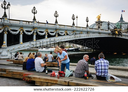PARIS, FRANCE - OCTOBER 4, 2014: Parisians and tourists have picnic and relax near Pont Alexandre III (Alexander III Bridge) and Grand Palace. Seine embankment is popular spot for picnic at weekends. - stock photo