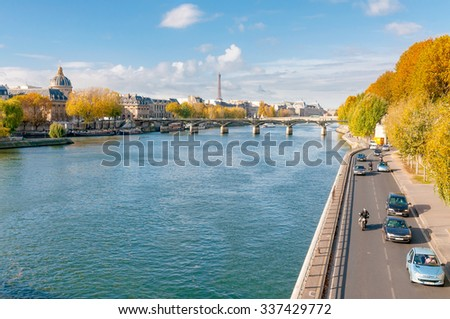 Paris/France - October 5, 2009: The Seine, the French Academy, the Pont des Arts and the Eiffel tower seen from the Pont Neuf in Paris. Houseboats moored at the dock. - stock photo