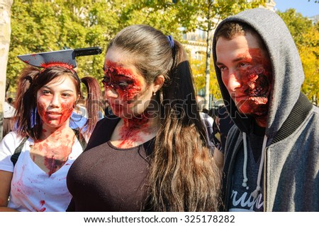 PARIS, FRANCE - OCTOBER 3, 2015: Three young people participating in Zombie parade at Place de la Republique (one of them with knife in head). Zombie Walk is an annual event in Paris. - stock photo